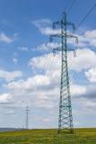 Wysokie woltaż linie energetyczne nad wiosny łąka Zdjęcia Stock