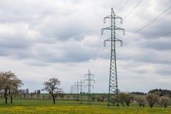 Wysokie woltaż linie energetyczne nad wiosny łąka Fotografia Royalty Free