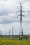 Wysokie woltaż linie energetyczne nad wiosny łąka Elektryczność słupy Zdjęcia Royalty Free