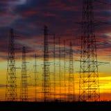 Wysokie woltaż linie energetyczne w półmroku Zdjęcia Stock
