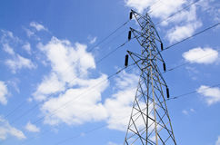 Wysokie woltaż linie energetyczne z elektryczność pilonami przy niebieskim niebem Zdjęcia Stock