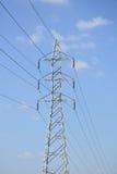 Wysokie woltaż linie energetyczne z elektryczność pilonami przy niebieskim niebem Fotografia Stock