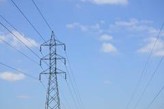 Wysokie woltaż linie energetyczne z elektryczność pilonami przy niebieskim niebem Zdjęcie Royalty Free