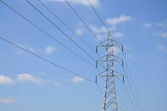 Wysokie woltaż linie energetyczne z elektryczność pilonami przy niebieskim niebem Zdjęcie Stock