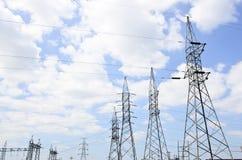 Wysokie woltaż linie energetyczne z elektryczność pilonami przy niebieskim niebem Obrazy Stock