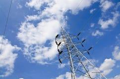 Wysokie woltaż linie energetyczne z elektryczność pilonami przy niebieskim niebem Fotografia Royalty Free