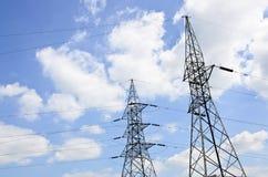 Wysokie woltaż linie energetyczne z elektryczność pilonami przy niebieskim niebem Obrazy Royalty Free