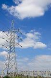 Wysokie woltaż linie energetyczne z elektryczność pilonami przy niebieskim niebem Obraz Royalty Free