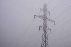 Wysokie woltaż linie energetyczne w ranek mgle Obrazy Royalty Free