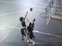 Wysokiego kąta widok młodzi Azjatyccy ludzie bawić się koszykówkę plenerową przy nocą obrazy stock