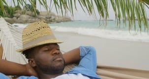 Wysokiego kąta widok amerykanin afrykańskiego pochodzenia mężczyzny dosypianie w hamaku na plaży 4k zdjęcie wideo