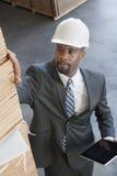 Wysokiego kąta widok amerykanina afrykańskiego pochodzenia męski kontrahent sprawdza drewniane deski podczas gdy trzymający pastyl Zdjęcie Royalty Free