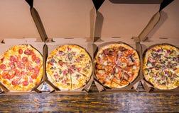 Wysokiego kąta widok cztery pizzy z rozmaitością polewy i chee Fotografia Stock