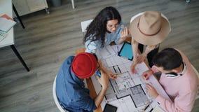 Wysokiego kąta widok grupa inżyniery dyskutuje budynku plan robi wysokości zbiory