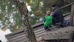 Wysokiego kąta widok ludzie i syna połów w stawie w lasowym obsiadaniu na krzesłach na drewnianych prąciach ojcuje mola i mienia zbiory