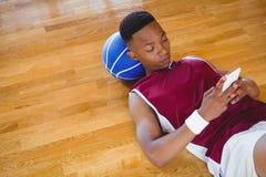 Wysokiego kąta widok męski gracz koszykówki używa telefon komórkowego Zdjęcia Royalty Free