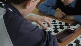 Wysokiego kąta widok ojciec i syn bawić się checker grę podczas gdy kłamający na podłoga w domu zdjęcie wideo