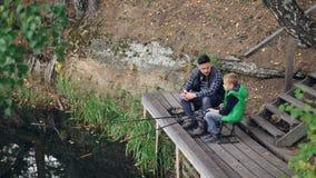 Wysokiego kąta widok rybak i jego dziecko chłopiec poważny połów od drewnianego mola obsiadania na krzesłach z prąciami i opowiad zbiory