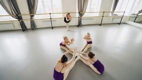 Wysokiego kąta widok skrzętni mali baletniczy tancerze ćwiczy przednich chyły siedzi na podłoga w pracownianym rozciąganiu i zbiory wideo