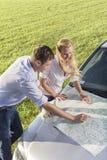 Wysokiego kąta widok pary czytania mapa na samochodowym kapiszonie podczas wycieczki samochodowej Fotografia Stock