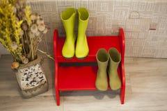 Wysokiego kąta zieleni podeszczowi buty na czerwieni dwa kroków drabinie Obraz Stock