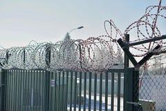 Wysokiego metalu ogrodzenie z ostrym drutem kolczastym na wierzchołku zakrywającym śniegiem w zimie jako symbol ograniczony dostę zdjęcie stock