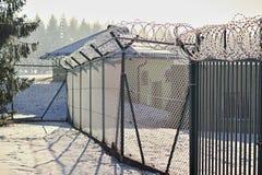 Wysokiego metalu ogrodzenie z ostrym drutem kolczastym na wierzchołku zakrywającym śniegiem w zimie jako symbol ograniczony dostę zdjęcia stock