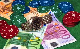 Wysokiego rolownika stosy w karcianej grą z lub grzebaku banknotami, kasyno układami scalonymi i wristwatch, obrazy royalty free