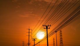 Wysokiego woltażu przekazu i słupa elektryczne linie z przy zmierzchu czasem pomarańczowym i czerwonym niebem architektura sylwet zdjęcia royalty free