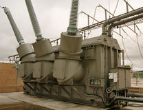 Wysokiego woltażu transformatorowy zbiornik, wieżyczki i popielaty niebo Zdjęcia Stock