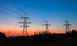 Wysokonapięciowe linie energetyczne podczas wschodu słońca Zdjęcie Royalty Free