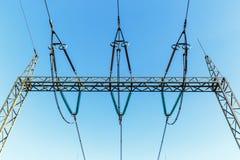 Wysokonapięciowi elektryczność pilony przeciw niebieskiemu niebu Obraz Royalty Free
