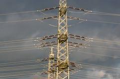 wysokonapięciowi elektryczność pilony przeciw podeszczowym chmurom Obrazy Royalty Free