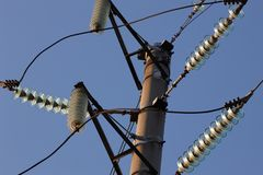 Wysokonapięciowy góruje przeciw niebieskiemu niebu Wysokonapięciowy electrica obraz stock