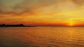 Wyspa w morzu przy pomarańczowym zmierzchem Obrazy Stock
