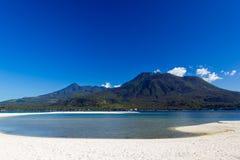 Wyspa z białym wulkanem w tle i piaskiem Fotografia Stock