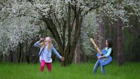 Występu dwa małe dziewczynki błaź się wokoło outdoors w wiośnie Sztuki muzyka rockowa w lesie wygłupy i imitacja strzelamy muzyka zbiory