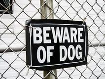 Wystrzegający się psa znak na siatki ogrodzeniu jako zabezpieczenia ostrzeżenie niebezpieczny rottweiler atak jeżeli trespassing obrazy stock