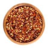Wysuszeni chili pieprzu płatki w drewnianym pucharze nad bielem Fotografia Royalty Free