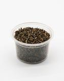 Wysuszeni czarni herbaciani liście w plastikowej filiżance odizolowywającej na bielu Obrazy Stock