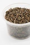Wysuszeni czarni herbaciani liście w plastikowej filiżance odizolowywającej na bielu Fotografia Royalty Free