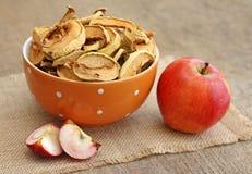 Wysuszeni jabłka w pomarańczowym pucharze na drewnianym tle Obrazy Stock