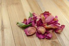 Wysuszeni różani płatki na drewnie Zdjęcia Stock