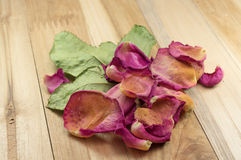 Wysuszeni różani płatki na drewnie Fotografia Stock