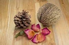 Wysuszeni różani płatki na drewnie z szyszkową sosną Zdjęcia Stock