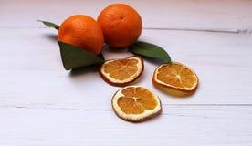 Wysuszeni tangerine plasterki i świeży tangerine na stole Obraz Stock