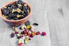 Wysuszona śliwka i winogrona w filiżance na czarny i biały tła odgórnym widoku horyzontalnym obrazy stock