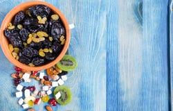Wysuszona śliwka i winogrona w suchej owoc na błękitnym Kopi i pucharze interliniujemy tło fotografia stock
