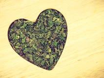 Wysuszona pokrzywa opuszcza serce kształtuje na drewnianej powierzchni Fotografia Stock