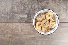 Wysuszone figi w pucharze na drewnianym tle Zdjęcia Royalty Free